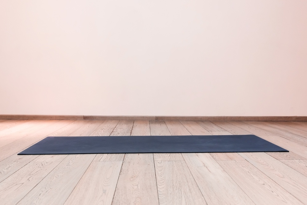 blue color yoga mat on floor